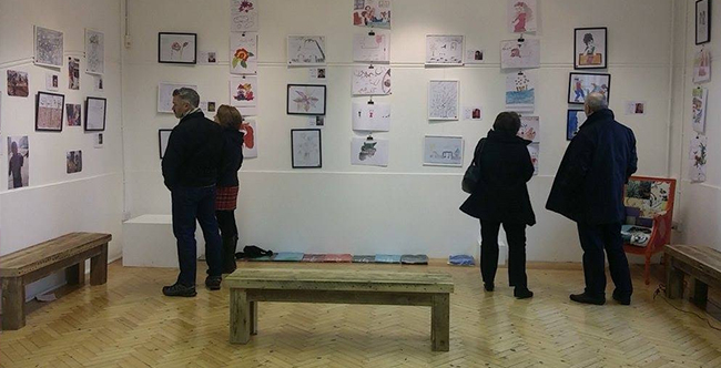 Visitors view artworks by refugee children during the Newton Abbot showing of the 'From Syria with Love' exhibition.